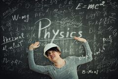 Physics formulas collapse. Young woman engineer looking up raising hands scared of huge amount of formulas about to collapse on head over blackboard background stock images