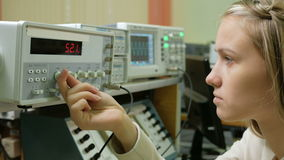 Young woman engineer student working in the lab with electric instrumentation. She carefully turns the wheel clock and stock video footage