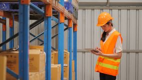 Young woman engineer using digital tablet checking stock in industrial warehouse stock video