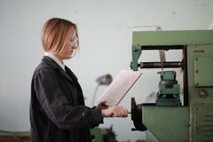 Young woman engineer working at machine tool stock photography