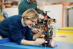 Young woman engineer working on robotics project. Young attractive women engineer working on robotics project royalty free stock images