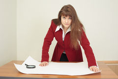 Young woman - engineer works with big drawing Royalty Free Stock Photography