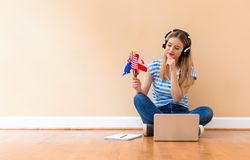 Young woman with English speaking country flags using a laptop. Computer against a big interior wall stock image