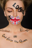 Young woman with english symbols on her face Royalty Free Stock Photos
