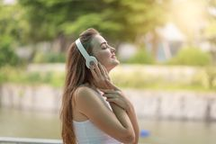 Young woman enjoy listening to music with headphones, happy and Royalty Free Stock Images