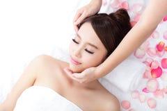 Young woman enjoy massage at spa. Beautiful young woman enjoy face massage at spa with roses, asian beauty Stock Photo