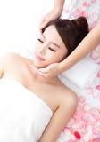 Young woman enjoy massage at spa. Beautiful young woman enjoy face massage at spa with roses, asian beauty Royalty Free Stock Images