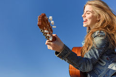 Young woman enjoy playing guitar. Blue sky background Stock Image