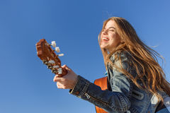 Young woman enjoy playing guitar. Blue sky background Stock Photo