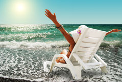 Young woman enjoy a sun on the coast sea. Happy woman in chaise lounge on the sea beach in sunny day Stock Images