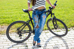 Young woman enjoy weather with her bike in city park at summer day Stock Photo