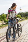 Young woman enjoy weather with her bike in city park at summer day Stock Image