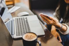 Young woman enjoy working on laptop and  coffee cup while sitting at his work place. Young Woman enjoy working at the Cafe for a coffee and to talk stock photos