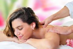 Young woman enjoying back massage. Stock Photo