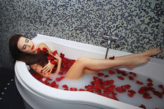 Young woman enjoying in the bathtub with rose petals Stock Image