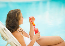 Young woman enjoying cocktail at poolside Stock Photography