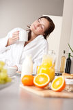 Young woman enjoying coffee in kitchen royalty free stock photography