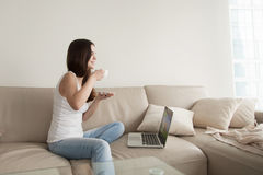 Young woman enjoying coffee on sofa with laptop, day off Stock Photography