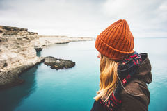 Young Woman enjoying cold sea view alone. Travel Lifestyle concept adventure vacations outdoor. Blonde girl wearing fashion orange knitted hat and scarf Stock Photos
