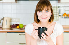 Young woman, enjoying a cup of coffee in her home. Stock Photography