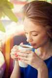 Young woman enjoying a cup of coffee in soft focus portrait Stock Images