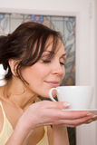 Young woman enjoying a cup of tea Royalty Free Stock Photos