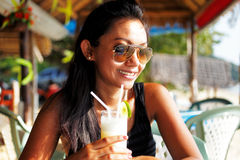 Young woman enjoying a drink in a beach restaurant in Thailand Stock Photo