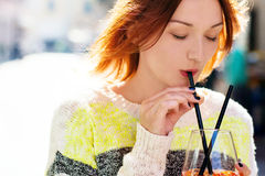 Young woman enjoying a drink on a sunny day. Young woman enjoying a orange drink - spritz - on a sunny day Stock Photography