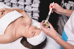 Young woman is enjoying facial procedure at beauty salon. Girl is lying in spa and getting clay mask with pleasure royalty free stock photos