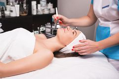Young woman is enjoying facial procedure at beauty salon. Girl is lying in spa and getting clay mask with pleasure stock photography