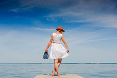 Young woman enjoying freedom at the beach. Young woman in white dress and hat enjoying summer at the beach royalty free stock photography
