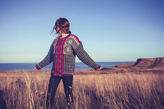 Young woman enjoying freedom in meadow by the sea Royalty Free Stock Photos