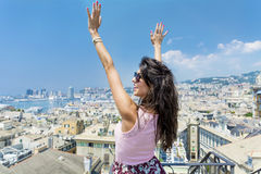 Young woman enjoying the freedom with open arms at  balcony over the city of Genova Stock Photography