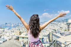 Young woman enjoying the freedom with open arms at  balcony over the city of Genova Royalty Free Stock Photography
