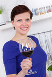 Young woman enjoying a glass of red wine in her kitchen. Young woman enjoying a glass of red wine in her modern kitchen Royalty Free Stock Photos