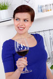 Young woman enjoying a glass of red wine in her kitchen. Young woman enjoying a glass of red wine in her modern kitchen Royalty Free Stock Images
