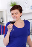 Young woman enjoying a glass of red wine in her kitchen Stock Images