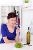 Young woman enjoying a glass of white wine in her kitchen Stock Image