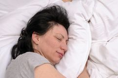 Young woman enjoying a good restful sleep. In her bed with her eyes closed and serene expression on comfortable clean white pillows viewed close up Royalty Free Stock Photos