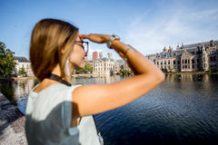 Woman in Haag, Netherlands. Young woman enjoying great view on the lake and old buildings in the centre of Haag city in Netherlands. Woman is out of focus Royalty Free Stock Images