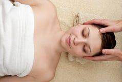 Young woman enjoying head massage at spa Stock Photos