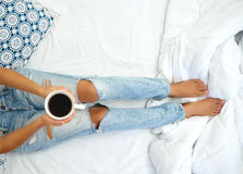 Young woman enjoying her coffee while sitting in bed. Stock Photography