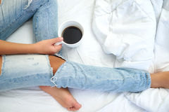 Young woman enjoying her coffee while sitting in bed. Royalty Free Stock Photos