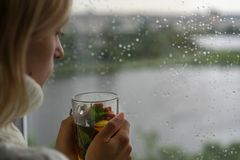 Young Woman Enjoying her morning tea, Looking Out the Rainy Window. Beautiful romantic unrecognizable girl drinking hot royalty free stock photo