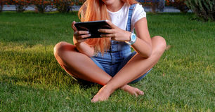 Young woman enjoying her time in park with tablet Royalty Free Stock Photo
