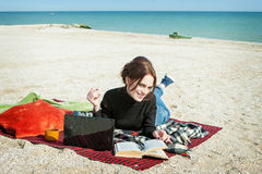 Young woman enjoying her working on the beach Royalty Free Stock Photos