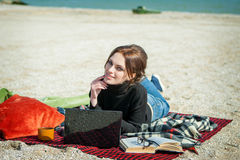 Young woman enjoying her working on the beach Royalty Free Stock Images