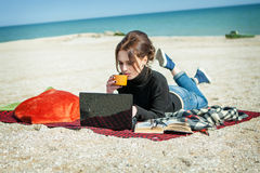 Young woman enjoying her working on the beach Stock Images