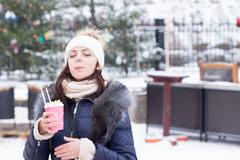 Young woman enjoying a hot drink in winter Royalty Free Stock Photography