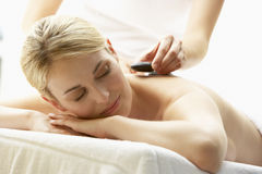 Young Woman Enjoying Hot Stone Treatment Stock Photo
